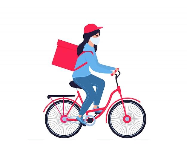 Corona-epidemie. het bezorgmeisje in een beschermend masker draagt voedsel op een fiets. geen verzendkosten.