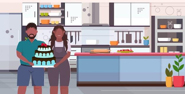 Coupe holding groot chocolade eigengemaakt cake zoet heerlijk overgewicht man vrouw vieren vakantie ongezond voeding zwaarlijvigheid concept modern keuken binnenlands portret horizontaal