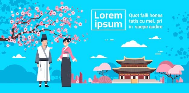 Couplein traditionele korea-kostuums over sakura blossom en het paleislandschap van korea