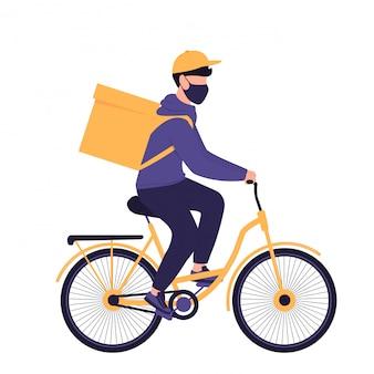 Covid-19. quarantaine. corona-epidemie. de bezorger in een beschermend masker draagt voedsel op een fiets. gratis verzending van eten.