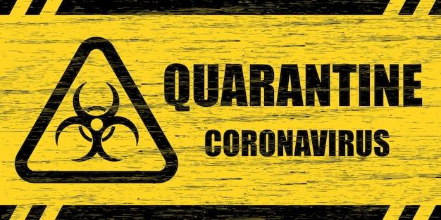 Covid-19 waarschuwingsbord. gekraste houten plaat met het opschrift quarantaine coronavirus en biohazard-symbool in gele en zwarte kleuren