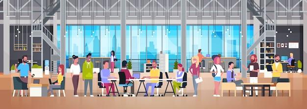 Coworking bureaugroep creatieve mensen die in modern medewerkerscentrum samenwerken