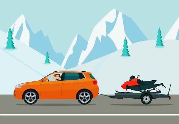 Cuv-auto met chauffeur sleept een aanhangwagen met een sneeuwscooter op een winterse weg.