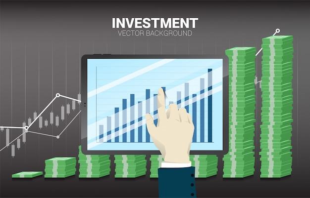 De aanrakingstablet van de zakenmanhand met stapel van bankbiljet en goede bedrijfsgrafiekachtergrond.