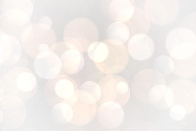 De abstracte witte achtergrond van bokeh gloeiende lichten
