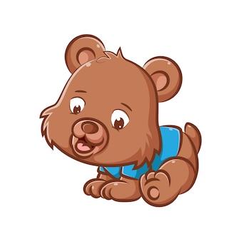 De afbeelding van de kleine beer met de bruine vacht gebruikt het blauwe shirt en probeert met zijn handen te kruipen