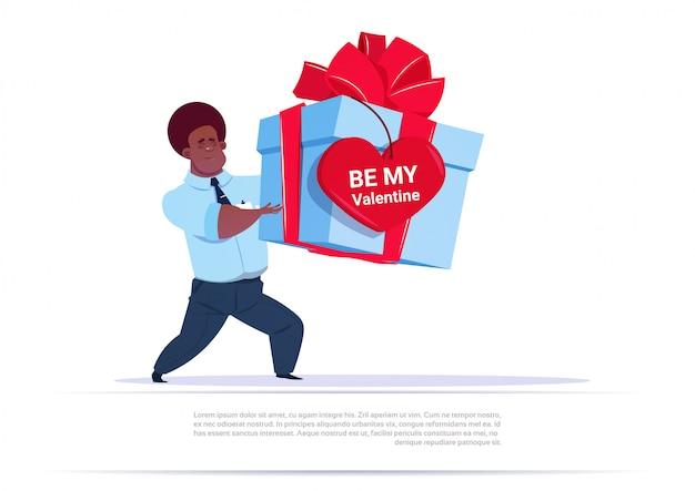 De afrikaanse amerikaanse mens die de grote doos van de gift met het etiket van de hartvorm houden is me de groet van de valentijnskaart over de achtergrond van het malplaatje