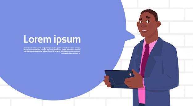 De afrikaanse amerikaanse tablet van de zakenmanholding spreekt grote praatjebel met de ruimte van het tekstexemplaar