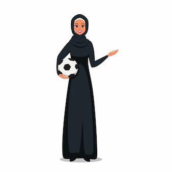 De arabische vrouw die hijab draagt houdt een voetbal in en toont bij iets met hand.