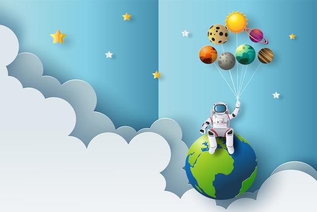 De astronaut zit op aarde met planeetballonnen in papierstijl. Premium Vector
