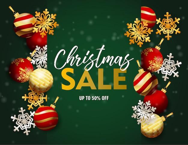 De banner van de kerstmisverkoop met ballen en vlokken op groene grond