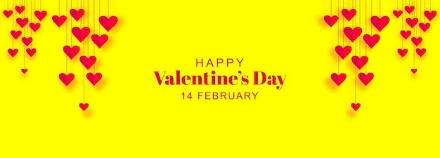 De banner van de valentijnskaartendag met hangende harten