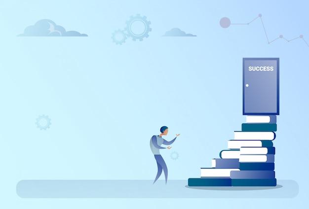 De bedrijfsmens beklimt boekenstapel aan de groeiconcept van de succesdeur