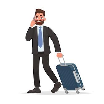 De bedrijfsmens op de luchthaven met bagage spreekt op de telefoon