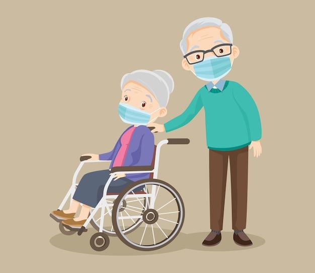 De bejaarde die medisch masker draagt, zit in een rolstoel en de oude man
