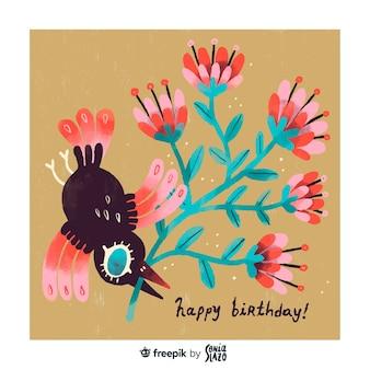 De bloemen van de vogelholding met de de groetkaart van de bekverjaardag