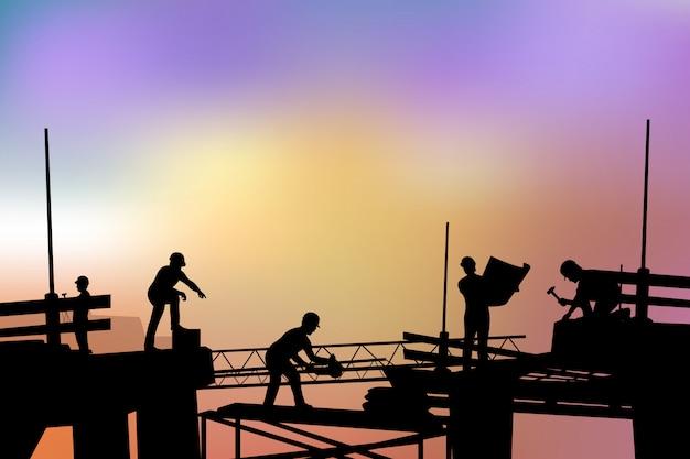 De bouwers silhouetteren bij zonsondergang