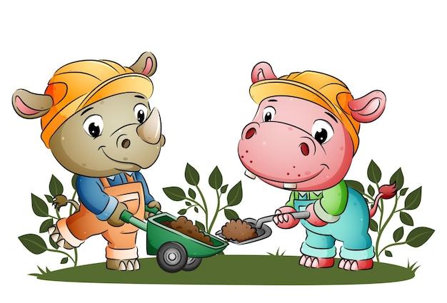 De bouwneushoorn en het nijlpaard verplaatsen de grond naar de kruiwagen van de illustratie