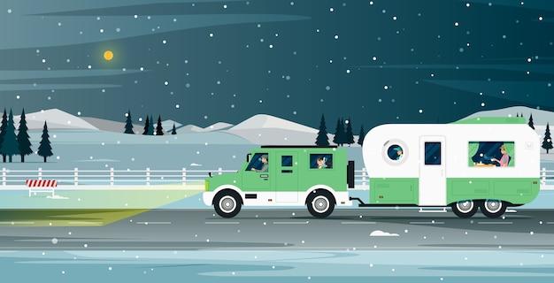 De caravanfamilie reist tijdens de sneeuwnacht