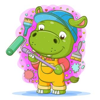 De cartoon van het groene nijlpaard gebruikt de gele overall en houdt de rolschilder vast