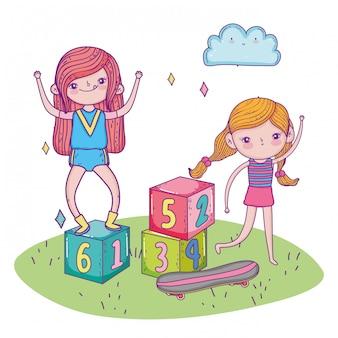 De dag van gelukkige kinderen, meisjes die met blokken en skateboardgras spelen