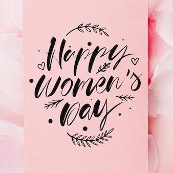 De dag van gelukkige vrouwen het van letters voorzien op bloemenachtergrond