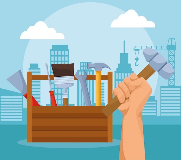 De doos en de hand die van reparatiehulpmiddelen een hamer over stedelijke stadsgebouwen houden