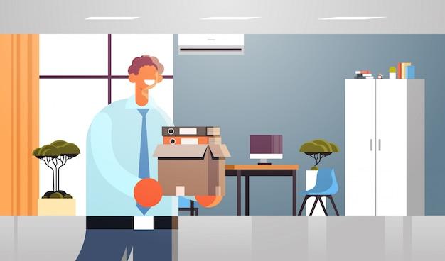De doos van de zakenmanholding met dingen dingen de gelukkige bedrijfsmens in formele van de de werkgelegenheidscreatie van de slijtage nieuw baan modern horizontaal binnenlands binnenlands portret