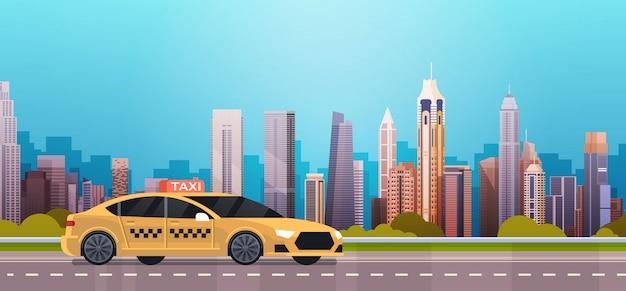 De gele cabine van de taxiauto op weg over de moderne achtergrond van de stad