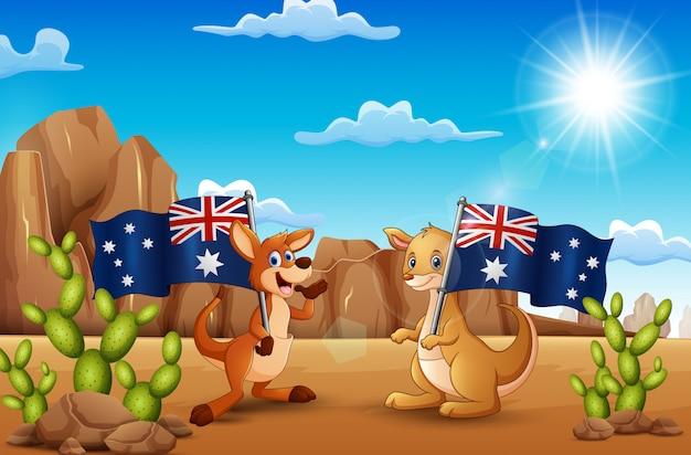 De gelukkige dag van australië met kangoeroes die een vlag in de woestijn houden