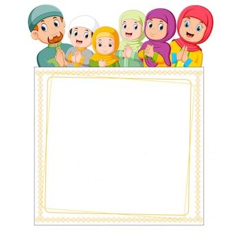 De gelukkige familie geeft de groet van ied mubarak op de bovenkant van leeg frame