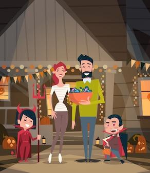 De gelukkige familie viert de ouders en de jonge geitjes van halloween dragen het concept van de de verschrikkingspartij van de vampierkostuums decoratie
