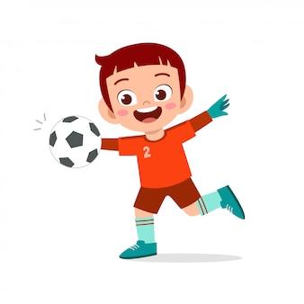 De gelukkige jongen speelt voetbal als keeper