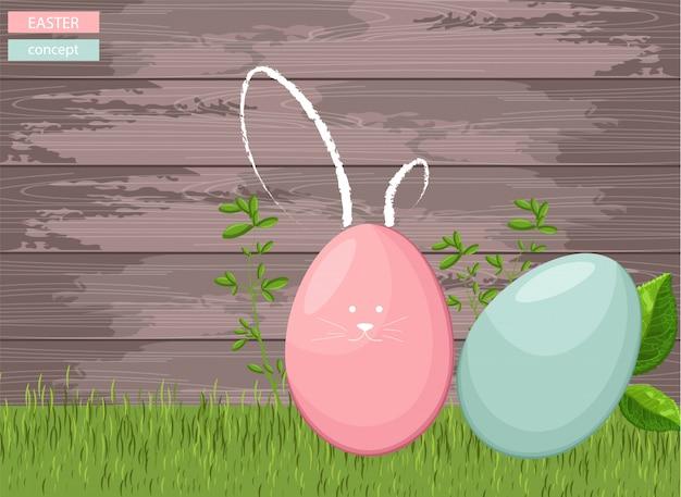 De gelukkige kleurrijke eieren van pasen op gras met houten achtergrond