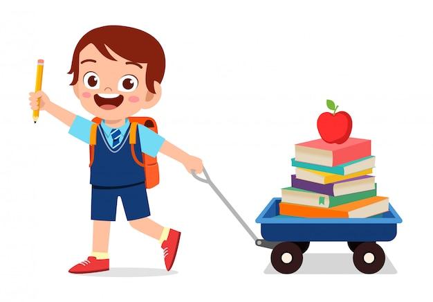 De gelukkige leuke jong geitjejongen brengt boek naar school