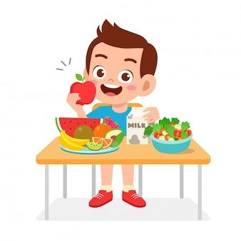 De gelukkige leuke jong geitjejongen eet gezond voedsel