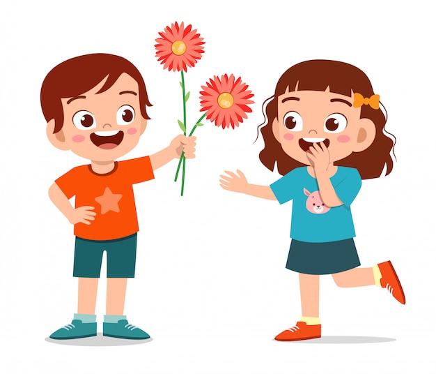 De gelukkige leuke jong geitjejongen geeft bloem aan vriend