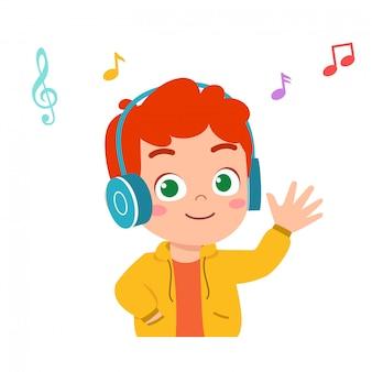 De gelukkige leuke jong geitjejongen luistert goede muziek