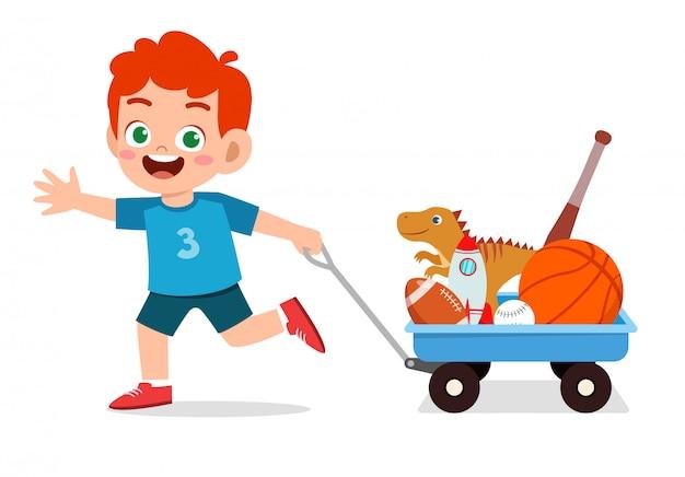 De gelukkige leuke jonge geitjejongen brengt stuk speelgoed met wagen
