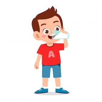 De gelukkige leuke jonge geitjejongen drinkt verse melk