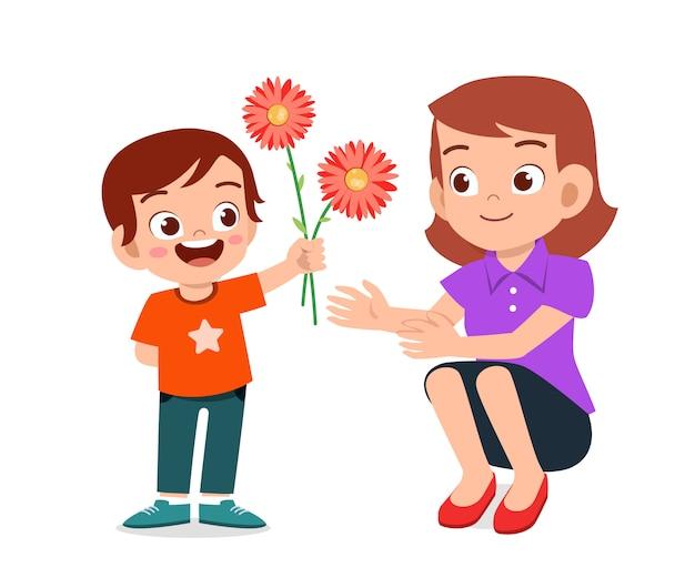 De gelukkige leuke jongen geeft bloem aan moeder