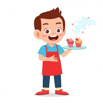 De gelukkige leuke jongen probeert cupcake te koken