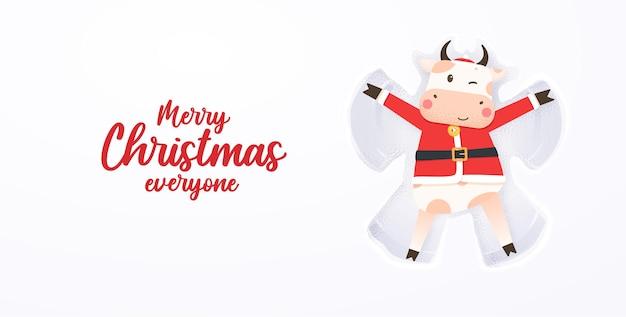 De gelukkige leuke stier in kerstmanhoed en kerstmankostuum die op met sneeuw bedekte grond liggen maakt sneeuwengel.