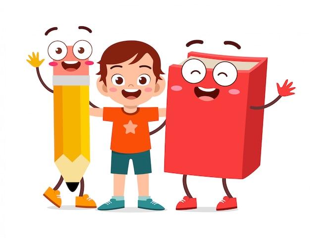 De gelukkige leuke tribune van de jong geitjejongen met boek en potlood