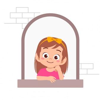 De gelukkige leuke uitdrukking van het jong geitjemeisje op venster