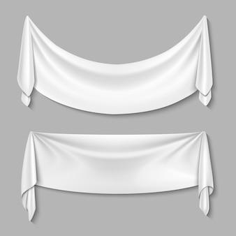 De gerimpelde textiel drapeert stoffen lege witte geplaatste banners. wit blad voor reclame