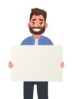 De glimlachende man houdt een lege poster vast. aanplakbiljet voor reclame.