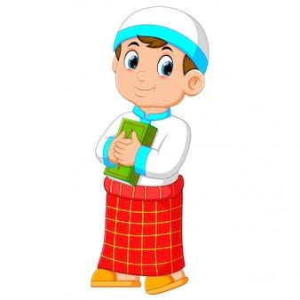 De goede jongen met de rode sarong houdt zijn groene al-koran op deze borst