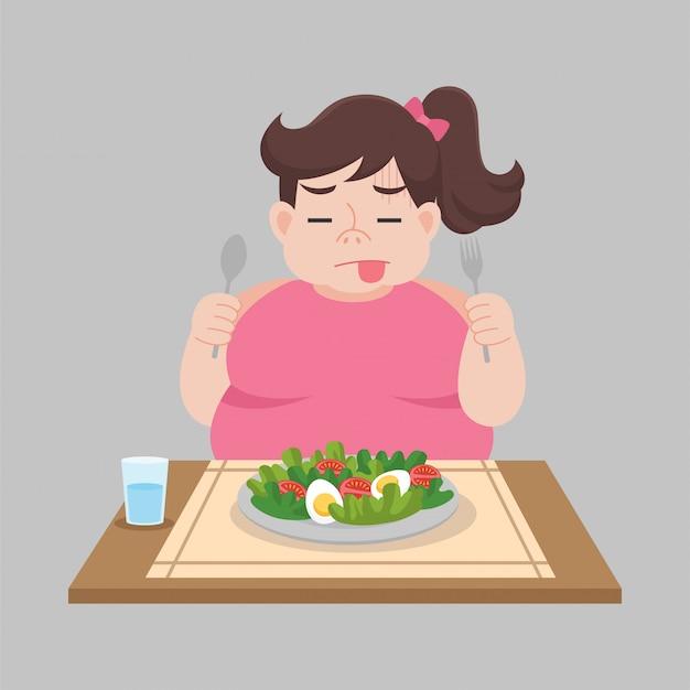 De grote gelukkige ongelukkige vrouw eet voedsel, groente, salade