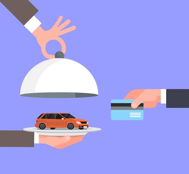 De hand die van de verkopersman voertuig op dienblad geven aan eigenaar met creditcard, autoverkoopverkoop of huurconcept